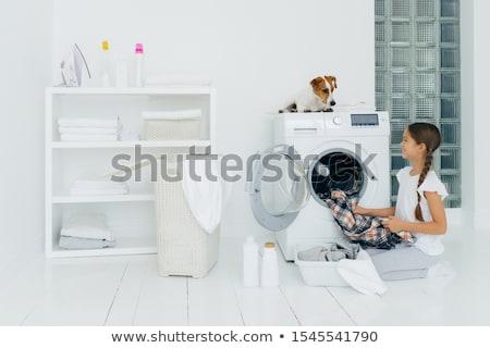 Positive girl emptying washing machine, holds clean checkered sh Stock photo © vkstudio