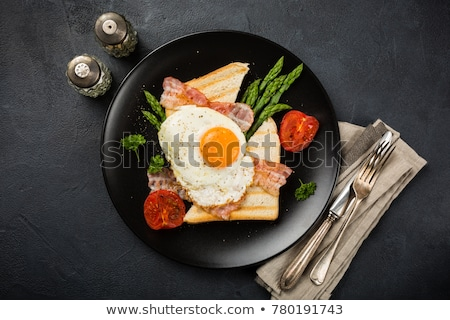 Breakfast or lunch with fried egg, bread toast, green asparagus, tomatoes and bacon Stock photo © Melnyk