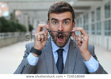 portrait of young handsome shocked good looking man working usin stock photo © hasloo