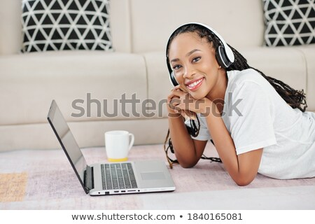 portrait of lying young woman with dreadlocks with headphones Stock photo © phbcz