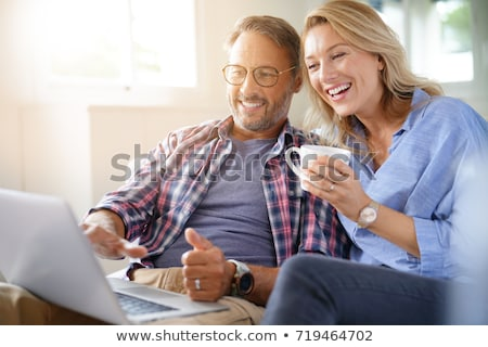 Stock photo: mature couple sitting on sofa with laptop
