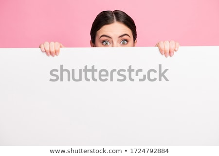 Stock photo: surprised young woman holding white empty paper isolated on white
