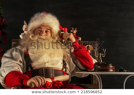 portrait of emotional santa claus calling phone at home stock photo © hasloo