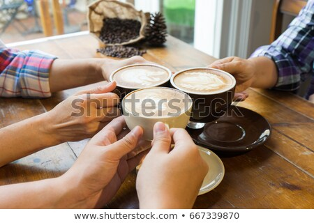 Smiling woman drinking coffee latte in cafe Stock photo © deandrobot
