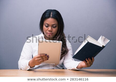 African woman choosing between tablet and book Stock photo © deandrobot