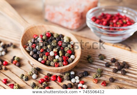 Mix of a pepper spice grains in a wooden spoon Stock photo © deandrobot