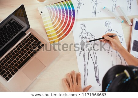 Cropped picture of young woman fashion illustrator drawing. Stock photo © deandrobot