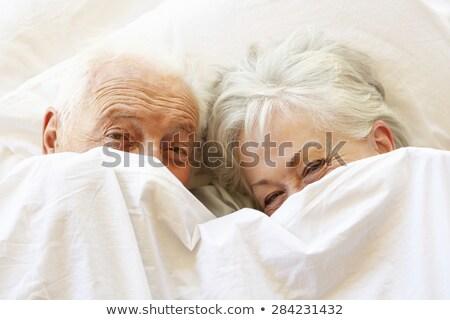 Szczęśliwy starszy para bed patrząc kamery kobieta Zdjęcia stock © wavebreak_media