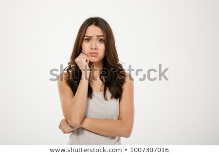 Confused brunette woman with arm near chin looking at camera Stock photo © deandrobot