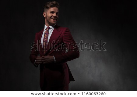 joyful man unbuttoning his red suit looks to side Stock photo © feedough