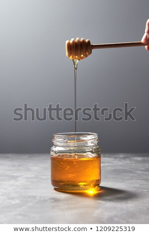 Wooden stick with natural flower honey in a womans hand above a gray concrete table. Rosh hashanah j Stock photo © artjazz