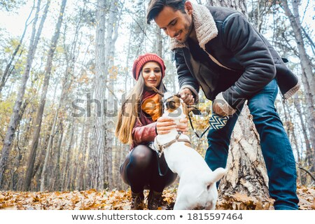 Woman and man walking their dog throwing a stick Stock photo © Kzenon