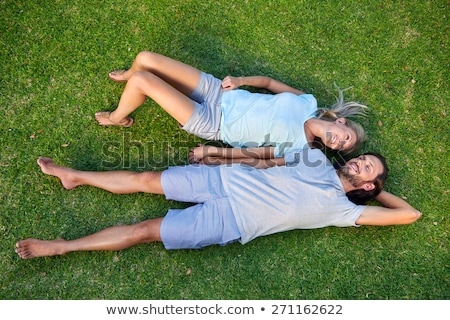 Happy young relaxed couple in love laying down on the grass overhead Stock photo © ruslanshramko