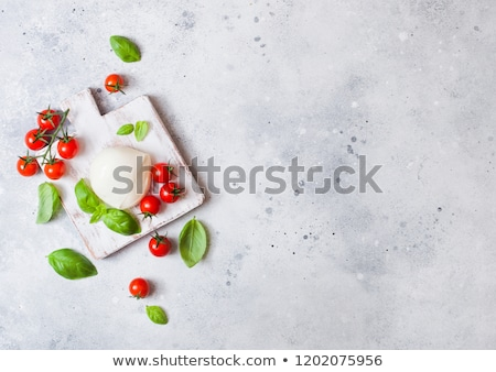 Fresh Mozzarella cheese on vintage chopping board with tomatoes and basil leaf with olive oil and tr Stock photo © DenisMArt