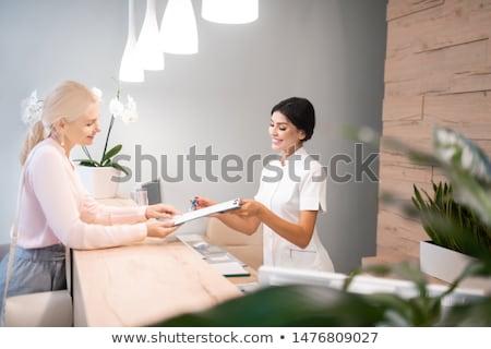 patient filling application form at dental clinic Stock photo © dolgachov