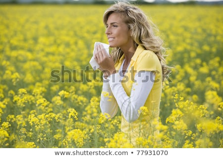 A Young woman sneezing in a field. Concept: seasonal allergy. Stock photo © Lopolo