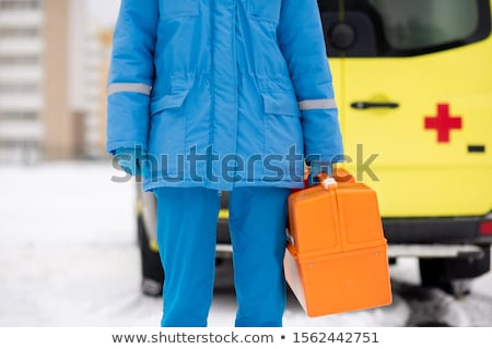 Young paramedic in blue workwear holding first aid kit with red cross Stock photo © pressmaster