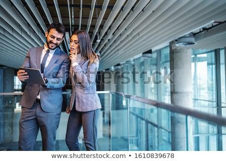 empresário · empresária · escritório · sorridente · olhando · indicação - foto stock © iofoto