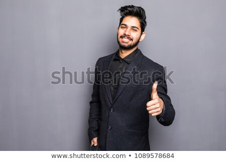 Portrait of a happy young man showing good job sign against whit stock photo © dacasdo