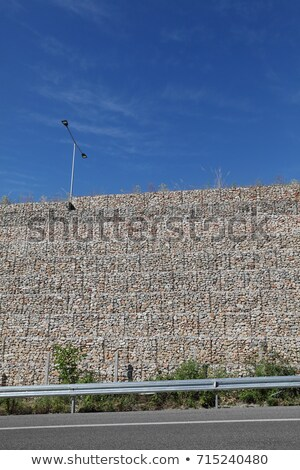Road embankment of gravel reinforced with steel mesh Stock photo © pzaxe