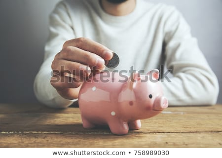Businessman Putting Coin Into Piggy Bank Stock photo © HighwayStarz