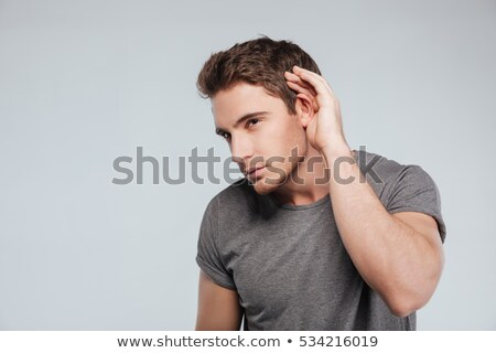 Curious handsome young man in plaid shirt overhearing rumors Stock photo © deandrobot
