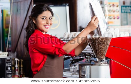 Indian barista filling coffee grinder Stock photo © Kzenon