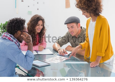 Stok fotoğraf: Creative Team Going Over Contact Sheets In Meeting