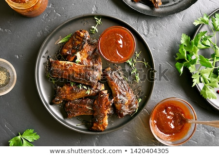 Roasted lamb ribs with spices and vegetables on black plate on d Stock photo © Yatsenko