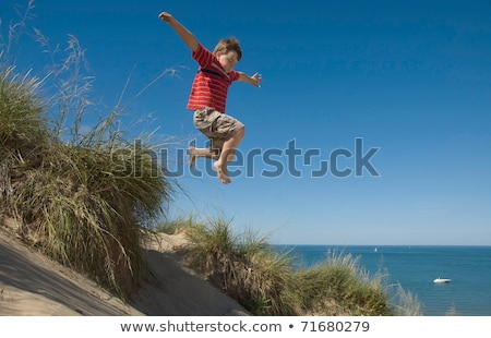 Boy jumping on sand dune Stock photo © IS2