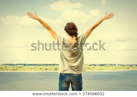 Young woman by river with arms out Stock photo © IS2