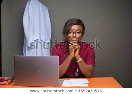 Female doctor relaxing at her desk. Stock photo © IS2