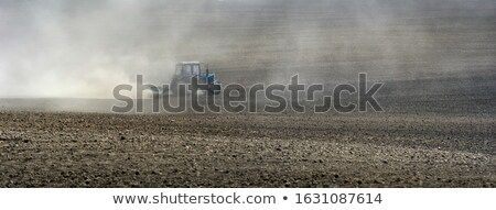 panoramic view of tractor plowing the soil after harvesting on the field top view from drone stock photo © artjazz