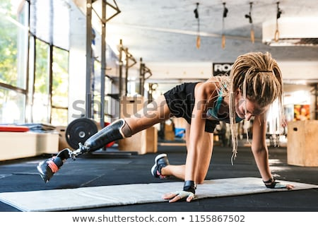 Disabled sports woman make sport stretching exercises in gym. Stock photo © deandrobot