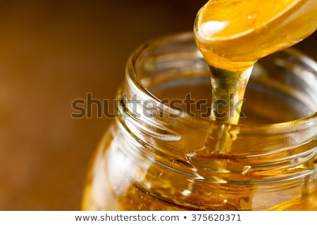 Wooden stick in a glass jar with fresh natural organic honey on a gray concrete table. Jewish New Ye Stock photo © artjazz