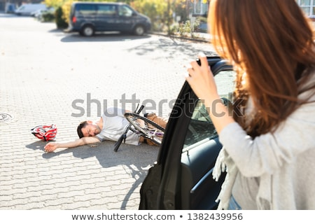 Woman Looking At Unconscious Male Cyclist Lying On Street Stock photo © AndreyPopov