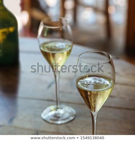 Elegant flute glass of sparkling white wine or champagne by side Stock photo © dashapetrenko