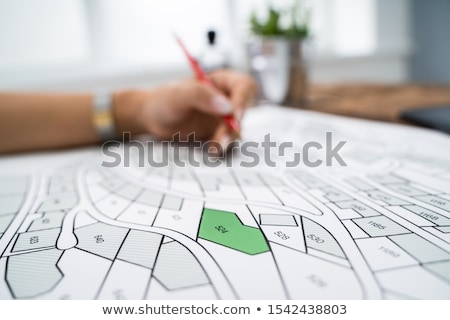 Human Hand Holding Pencil Over Cadastre Map Stock photo © AndreyPopov