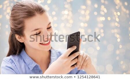 girl messaging on smartphone over festive lights Stock photo © dolgachov