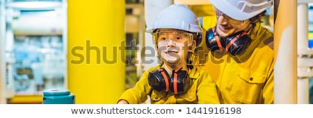 Young man and a little boy are both in a yellow work uniform, glasses, and helmet in an industrial e Stock photo © galitskaya