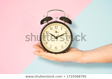 Woman holding a clock against background with clock Stock photo © wavebreak_media