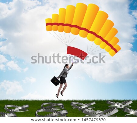 Businesswoman falling into trap on parachute Stock photo © Elnur