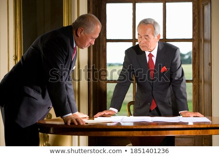 Businessman leaning over office desk studying Stock photo © lichtmeister