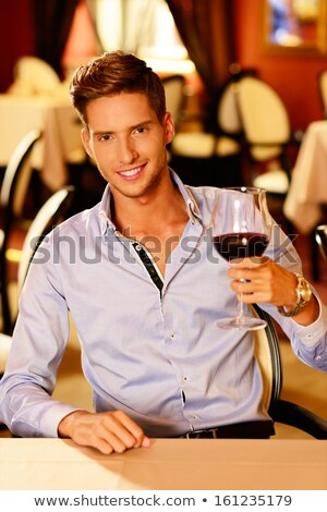 handsome young man sitting by the table and drinking red wine in stock photo © boggy