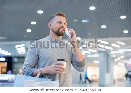 Young man with smartphone, drink and paperbags calling online shop Stock photo © pressmaster