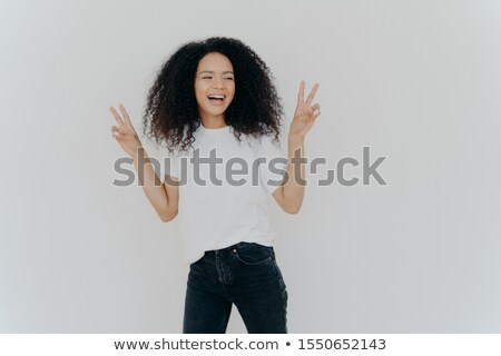 Carefree woman with Afro hairstyle raises hands up, shows victory gesture or peace sign, looks gladf Stock photo © vkstudio