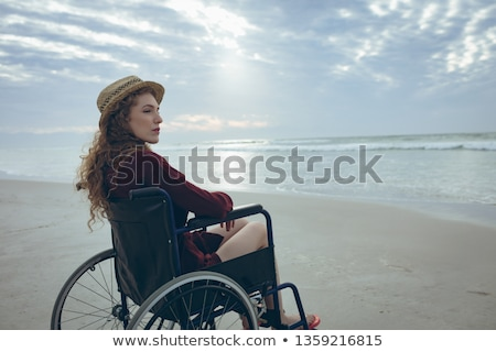 Side view of young disabled Caucasian woman sitting on wheelchair at beach. She is looking away Stock photo © wavebreak_media