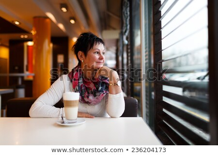 A woman with short hair drinks coffee and looks through the window Stock photo © ElenaBatkova