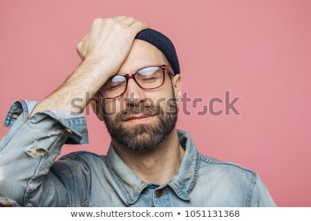 Portrait of depressed middle aged unshaven male closes eyes and keeps hand on forehead, has unhappy  Stock photo © vkstudio