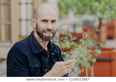 Outdoor shot of good looking male with dark beard and moustache, being in good mood, spends leisure  Stock photo © vkstudio